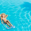 Stock Photo: Womrelaxing at swimming pool