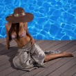 Stock Photo: Woman by the swimming pool