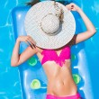 Young woman on a lilo in the swimming pool — Stock Photo #29777643