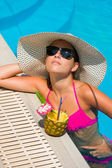 Woman with fresh cocktail in the swimming pool — Stock Photo