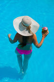 Woman with fresh cocktail in the swimming pool — Stok fotoğraf