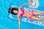 Young woman on a lilo in the swimming pool — Stock Photo