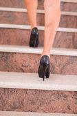 Swoman taking step on stairway — Stock Photo