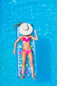 Młoda kobieta na lilo w basenie — Zdjęcie stockowe