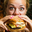 Woman eating a cheeseburger — Stock Photo