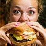 Woman eating a cheeseburger — Stock Photo
