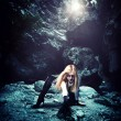 Woman with dragon in a cave — Stock fotografie