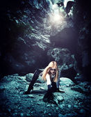 Woman with dragon in a cave — Stock Photo