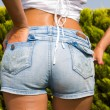 Girl in jeans shorts at the park — Stok fotoğraf