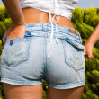 Girl in jeans shorts at the park — Foto de Stock