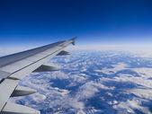 Airplane flying above the clouds — Stock Photo