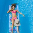 A girl is relaxing in a swimming pool — Stock Photo #37403977