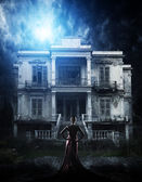 Woman in red dress at haunted house — Stock Photo
