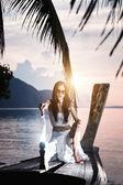 Mujer en barco de madera largas cola con un cuchillo — Foto de Stock