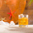 Stock Photo: Whisky liqueur glass with ice cubes on beach