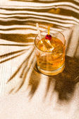 Whisky liqueur glass with ice cubes on the beach — Stock Photo