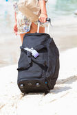 Vacation Woman dragging her  Suitcase on the beach — Stock Photo