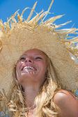 Blonde  wearing straw hat on a beautiful sunny beach — Stock Photo