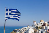 Greek flag with overview on Oia on the island of Santorini — Stock Photo