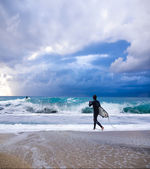 Young male surfer standing looking out at ocean. — Stock Photo