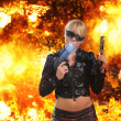 Hot blonde woman with gun over explosion — Stock Photo #45035673