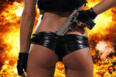 Hot blonde woman with gun over explosion  — Foto Stock