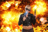 Hot blonde woman with gun over explosion  — Foto de Stock