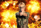 Hot blonde woman with gun over explosion  — Stockfoto
