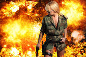 Hot blonde woman with gun over explosion  — Stok fotoğraf
