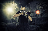 Man with a gun and wearing sunglasses — Stock Photo