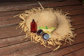 Hat, sunglasses and suntan lotion on the deck  — Stockfoto