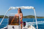Summer vacation - young girl driving a motor boat — Stok fotoğraf