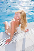 Pretty blonde woman relaxing at the swimming pool  — Stock Photo