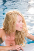 Pretty blonde woman relaxing at the swimming pool — Стоковое фото