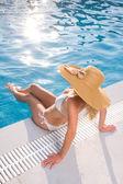 Beautiful young woman at summer swimming pool — Stock Photo