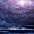 Lightning flashes across the beach from a storm — Foto Stock
