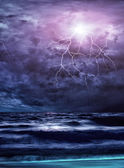Lightning flashes across the beach from a storm — Stock Photo