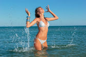 Beautiful woman jumps out of the sea  big splash — Stock Photo