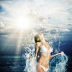 Beautiful woman jumps out of the sea  big splash — Stock Photo #49111047