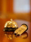Hotel bell and key lying on the desk — Stock Photo