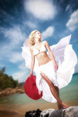 Young woman in white bikini holding sarong on the beach — Stock Photo