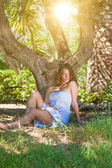 Lady wearing elegant white dress relaxing in the forest  — Foto de Stock