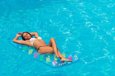 A girl is relaxing in a swimming pool — 图库照片