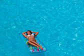 A girl is relaxing in a swimming pool — ストック写真