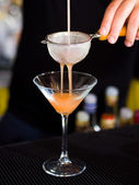 Bartender pooring cocktail into Martini glass — Stock Photo
