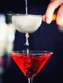 Bartender pooring cocktail into Martini glass — 图库照片