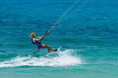 A young woman kite-surfer rides in greenish-blue sea  — Stock Photo