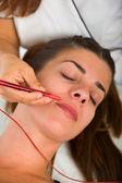 Paciente do sexo feminino atraente recebendo eletroacupuntura no rosto — Fotografia Stock