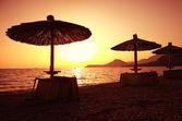 Hermosa playa con tumbonas y sombrillas al atardecer — Foto de Stock