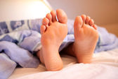 Bare feet in bed — Stock Photo